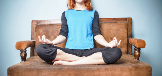 Spiritual young woman is meditating on an old sofa